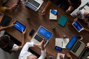 Plusieurs personnes travaillent ensemble sur un grand bureau
