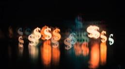 Signes dollars avec effet de lumière et de flou sur fond noir