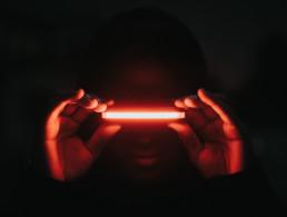 Personne dans le noir avec un laser rouge vertical au niveau des yeux