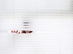 Personne regardant à travers les stores d'une fenêtre