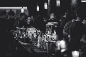 Photo prise derrière le comptoir d'un bar plein (noir & blanc)