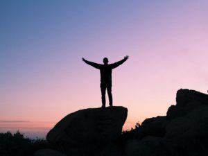 Seul au sommet d'un rocher bras levés devant la mer au coucher de soleil