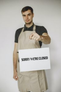 """Jeune homme avec un tablier tenant une pancarte """"Sorry we're closed"""""""