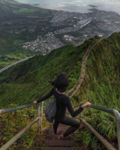 Femme au sommet d'un escalier surplombant la forêt et la ville
