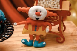 Clown en peluche appuyé sur un paquet de popcorn