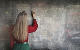 Femme de dos expliquant un problème mathématique sur un tableau en ardoise