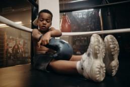 Petit garçon assis au coin d'un ring de boxe